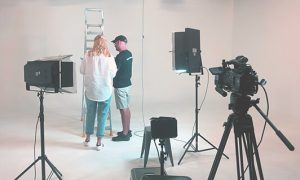 two people with back to camera in a white studio